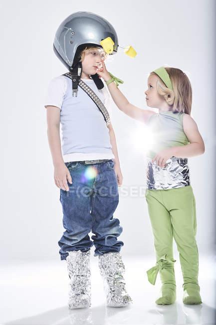 Девушка и мальчик, одетые как пришельцы и космонавты — стоковое фото