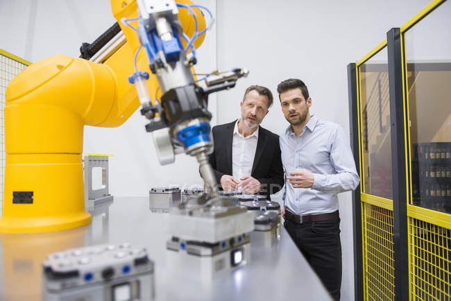 Geschäftsleute beobachten Industrieroboter — Stockfoto