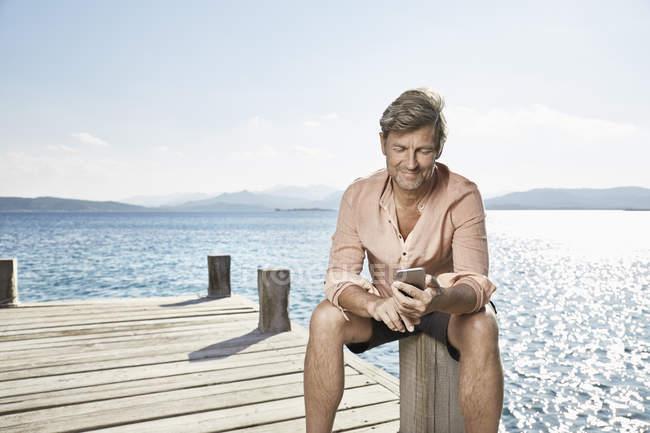 Homme souriant assis sur la jetée — Photo de stock