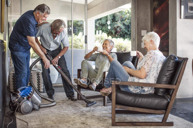 Senior men vacuming house — Stock Photo