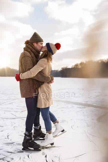 Конькобежцы целуются на замерзшем озере — стоковое фото