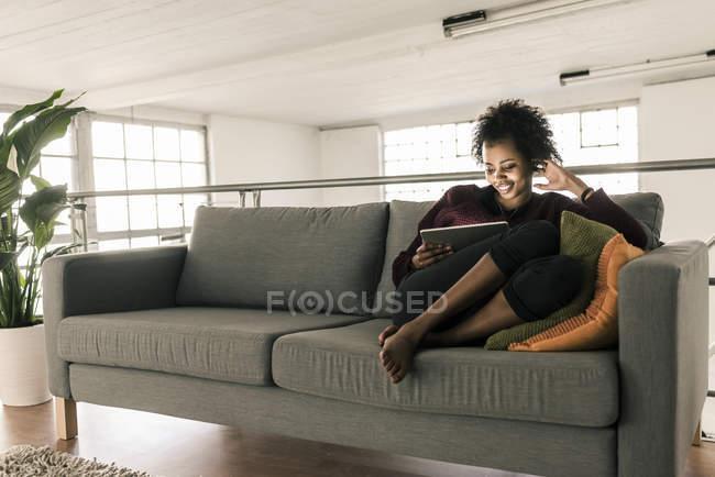 Jeune femme souriante assise sur le canapé et utilisant une tablette — Photo de stock