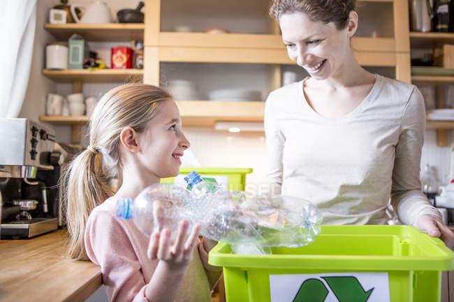 Madre e hija en el hogar separar residuos - foto de stock