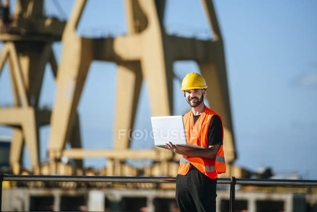 Trabalhador do porto sorrindo usando laptop — Fotografia de Stock
