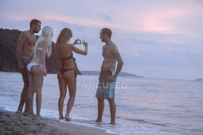 Cuatro amigos en la playa tomando fotos - foto de stock