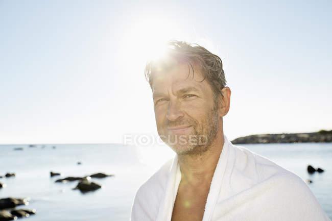 Hombre con toalla frente al mar - foto de stock