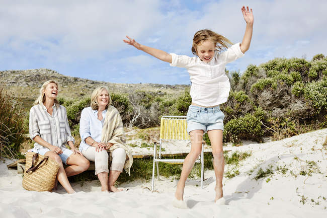 Girl jumping for joy on beach — Stock Photo