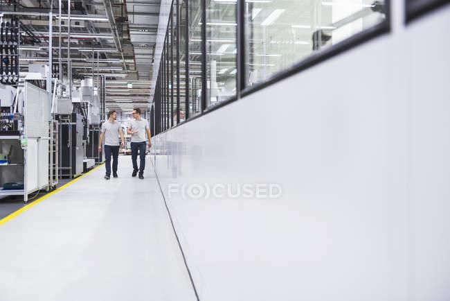 Мужчины ходят и разговаривают на фабрике — стоковое фото