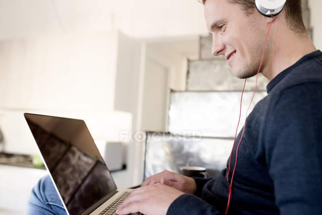 Smiling man using laptop — Stock Photo