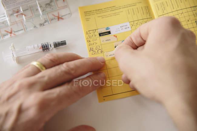 Mãos colocando adesivo no passe de vacinação — Fotografia de Stock