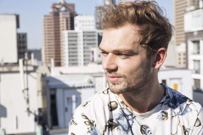 Молодой человек на террасе смотрит в сторону — стоковое фото