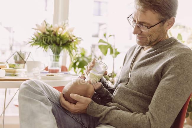 Father feeding newborn — Stock Photo