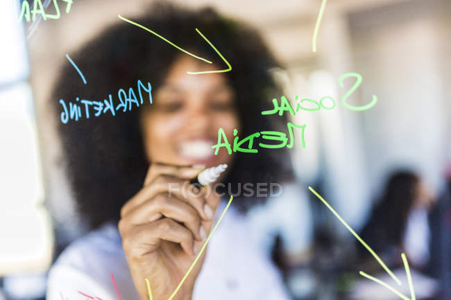 Businesswoman writing on glass — Stock Photo