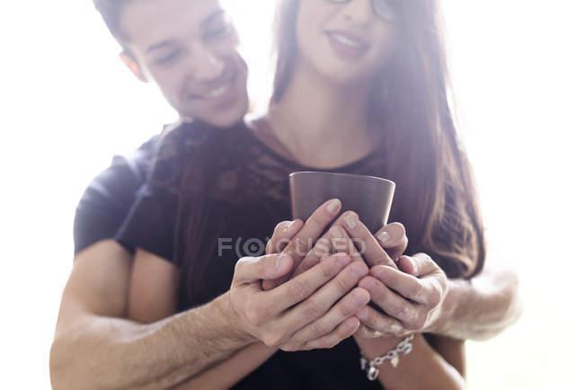 Jovem casal segurando xícara de café — Fotografia de Stock