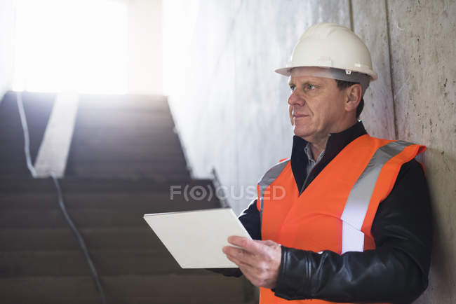 Man using tablet in building under construction — Stock Photo