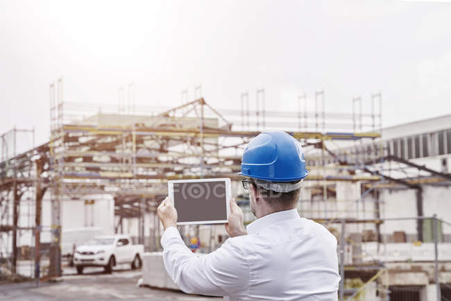 Man taking picture at construction site — Stock Photo