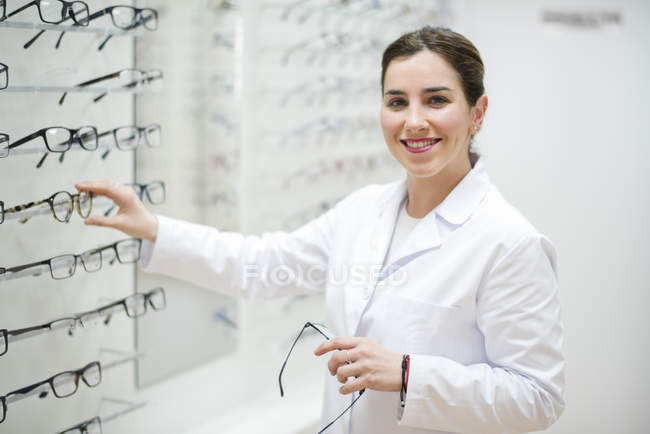 Optician arranging glasses frames in shop — Stock Photo