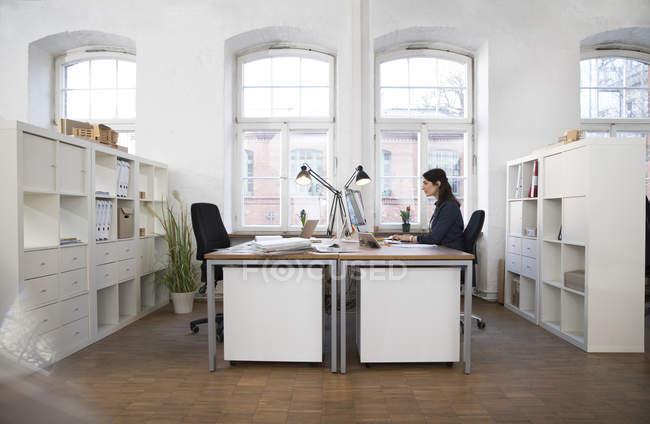 Femme travaillant sur ordinateur au bureau — Photo de stock