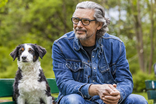 Man sitting with dog on bench — Stock Photo