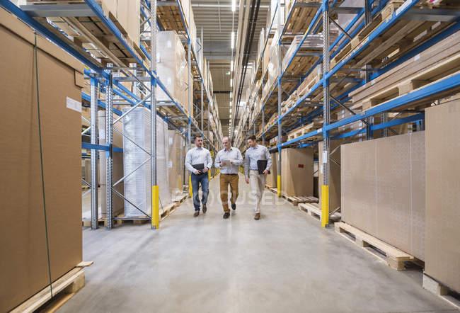 Hommes qui marchent dans l'entrepôt de l'usine — Photo de stock