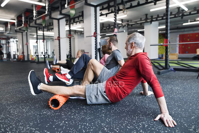 Seniors using foam rollers in gym — Stock Photo