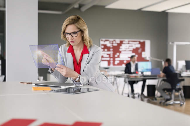 Businesswoman using futuristic portable device — Stock Photo