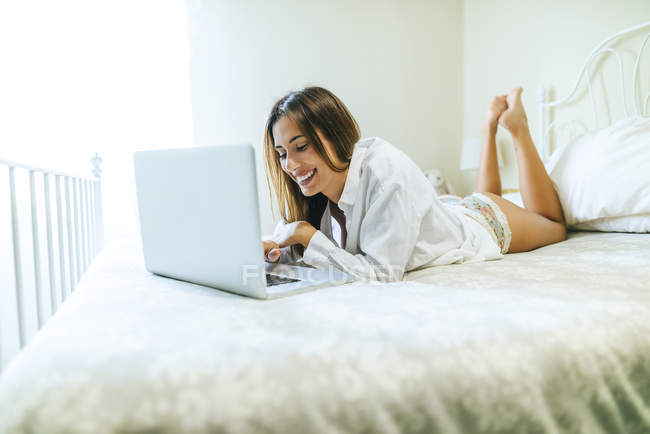 Woman lying on bed and using laptop — Stock Photo