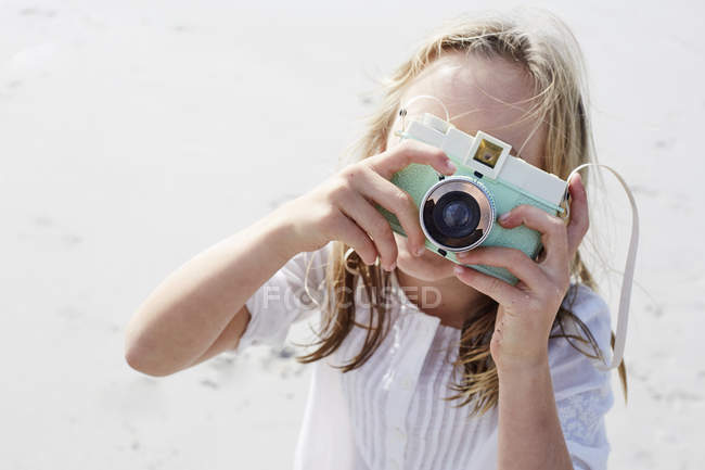 Girl taking picture with camera — Stock Photo