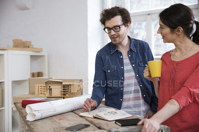 Man and woman discussing draft in office — Stock Photo