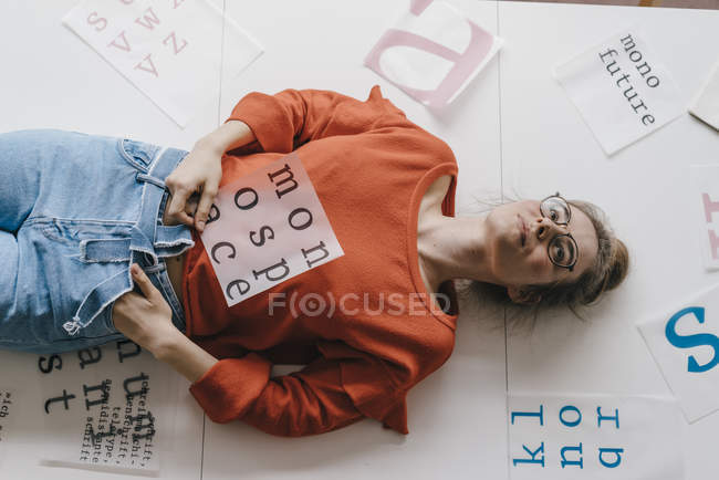 Woman lying surounded by letter templates — Stock Photo