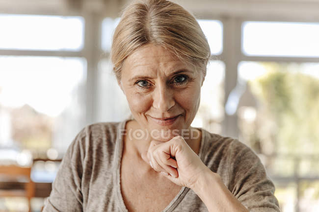 Smiling woman sitting at home — Stock Photo