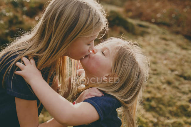 Blond sisters kissing outdoors — Stock Photo