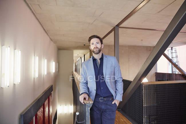 Geschäftsmann steht auf Büroflur — Stockfoto
