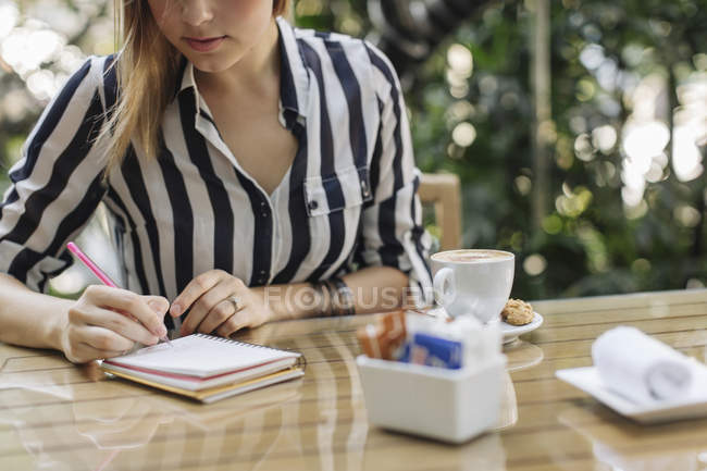Woman sitting at cafe writing in notebook — Stock Photo