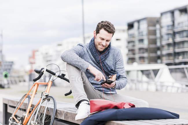 Empresário com bicicleta usando smartphone — Fotografia de Stock