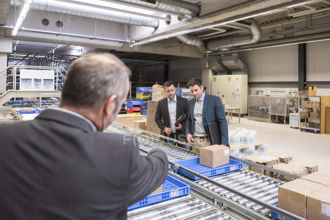 Бизнесмены, стоя на ленточный конвейер — стоковое фото