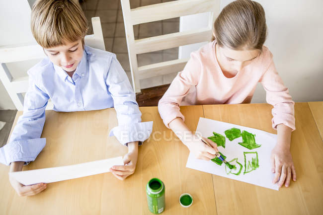 Brother and sister painting recycling symbols — Stock Photo