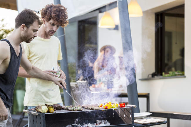 Two men at barbecue grill — Stock Photo