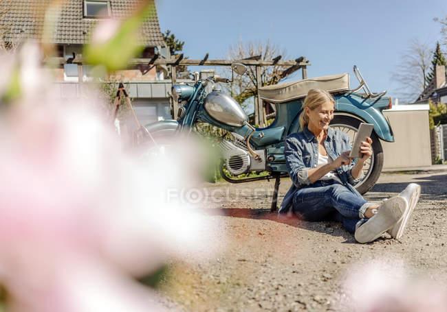 Femme assise sur le sol avec tablette — Photo de stock