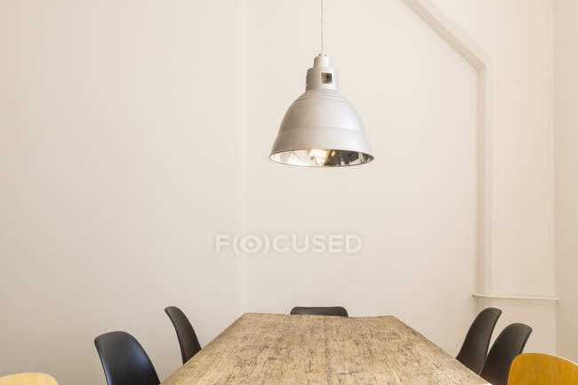 Conference table and ceiling light in a loft — Stock Photo