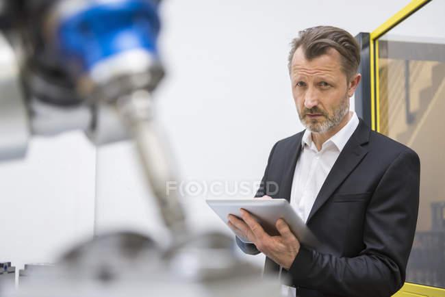 Homem de negócios controlando robôs industriais — Fotografia de Stock