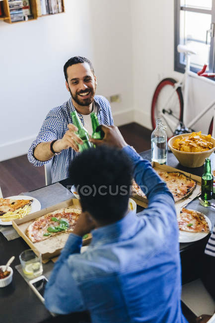 Friends clinking beer bottles — Stock Photo