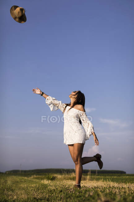 Woman throwing hat in air — Stock Photo