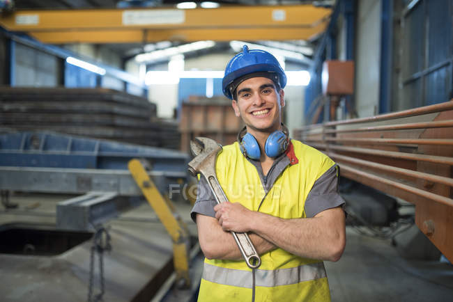 Smiling man holding wrench in factory — Stock Photo