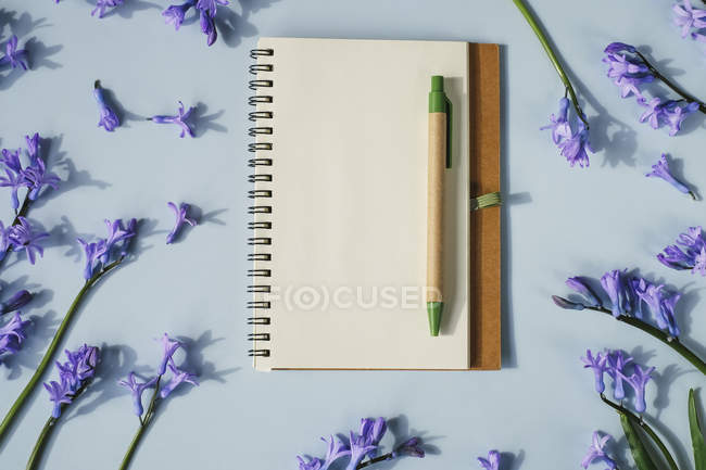 Notebook with pen and flowers — Stock Photo