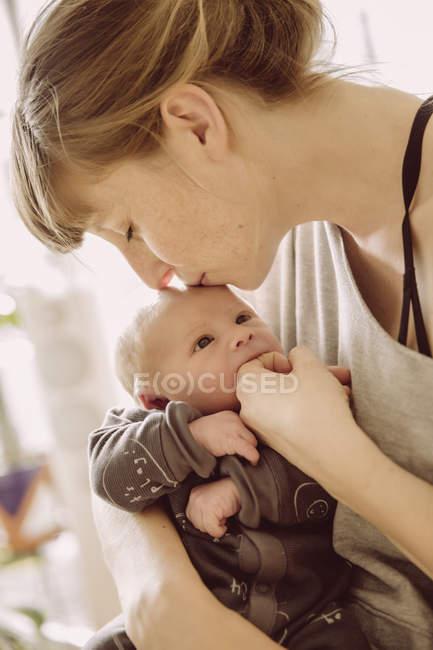 Madre besando bebé recién nacido - foto de stock