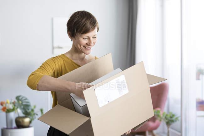 Женщина распаковывает посылку — стоковое фото