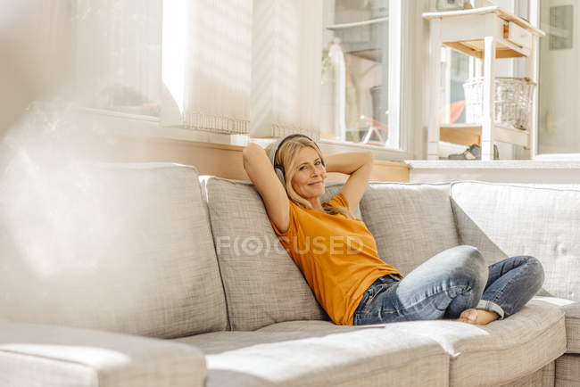 Donna seduta sul divano con le cuffie — Foto stock