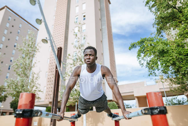 Человек делает отжимания на спортивной земле — стоковое фото