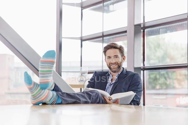 Businessman putting feet on table — Stock Photo